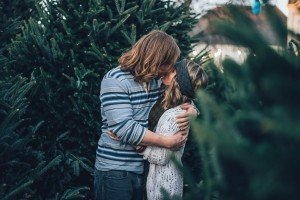 couple-kissing-among-trees-in-garden